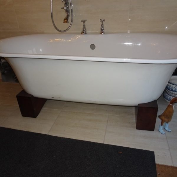 Roll top bath on wooden blocks for sale